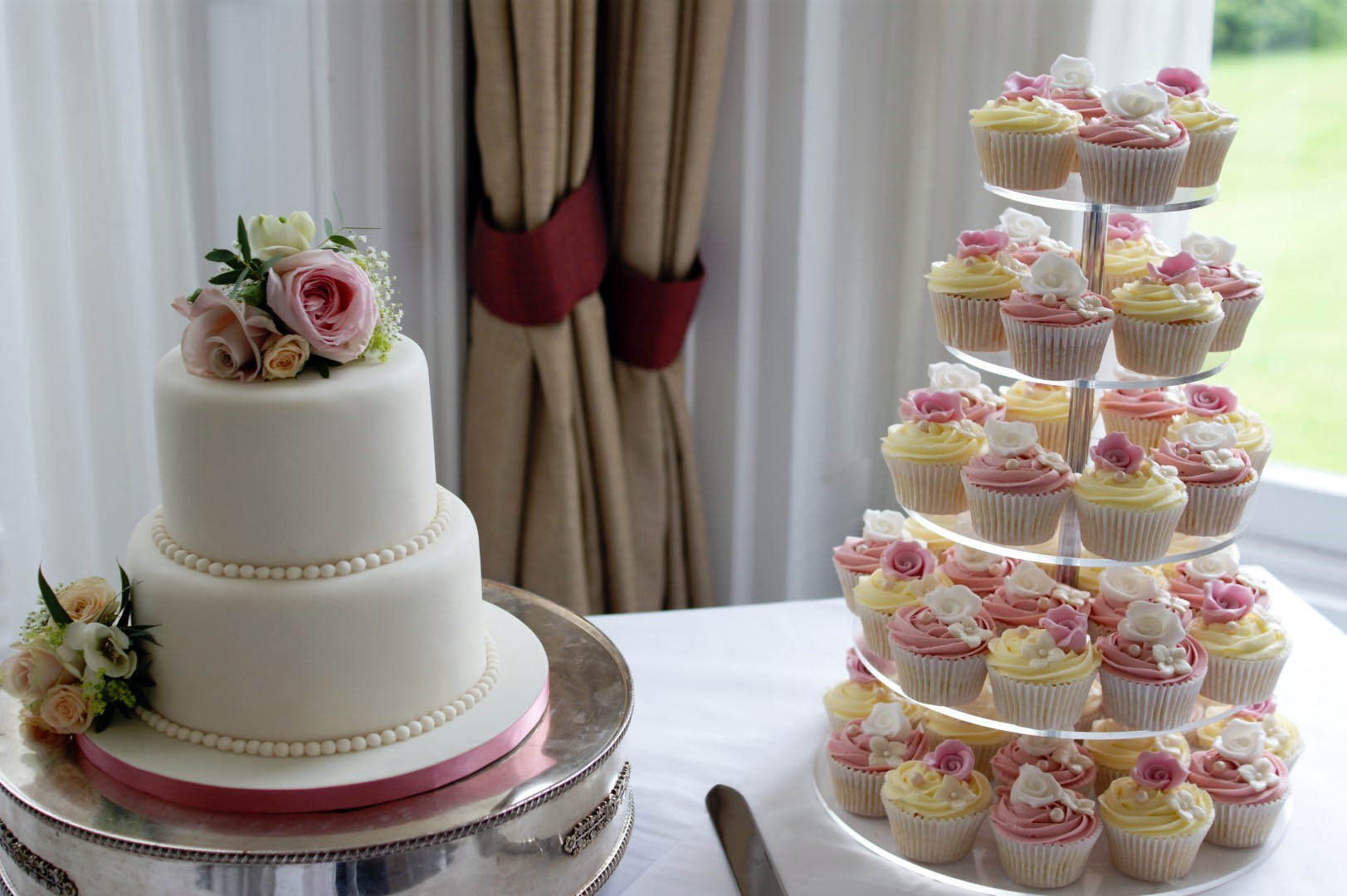 White Floral Wedding Cake With Cupcakes Bakealous