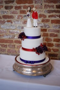 white 3 tier wedding cake with cadbury purple ribbon and bride and groom cake topper